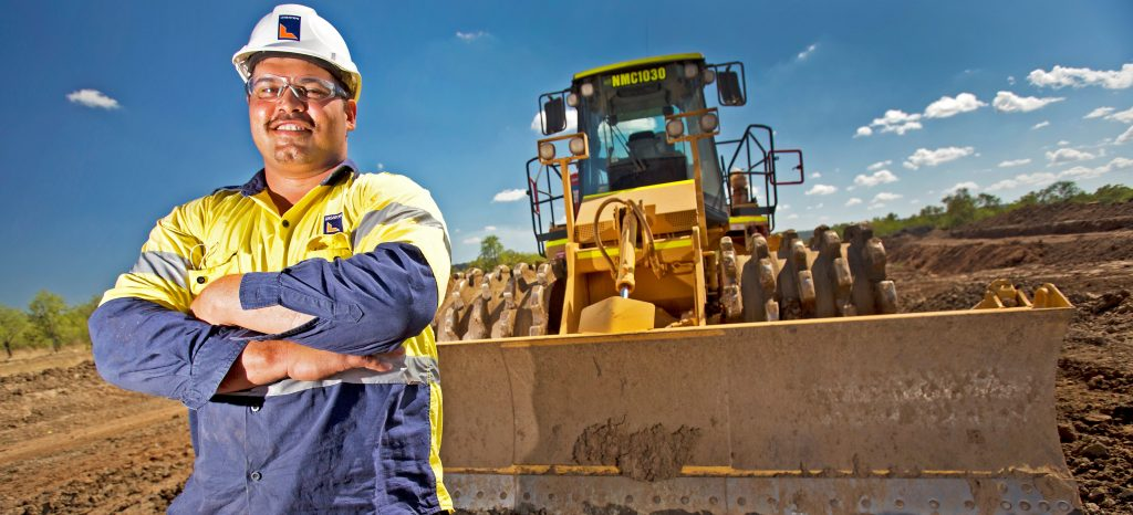Worker in front of a compactor on site at the Ord East Kimberley Expansion